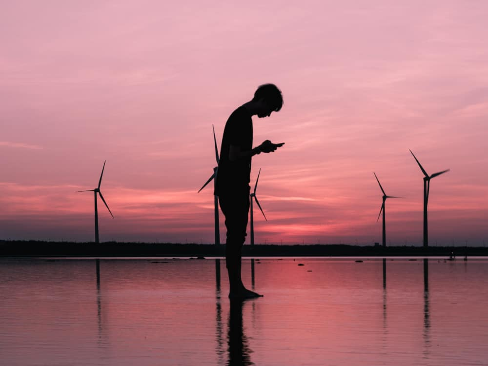 Man with mobile phone in front of wind turbines